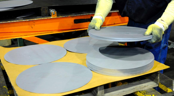 Four stacks of circular steel blanks with someone adding an additional blank to a stack