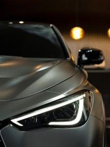 Close-up of a sliver luxury car, illuminated in a dark garage. The steel curves of the car catch the soft, warm light.