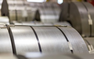 This image is a close up on a roll of advanced high-strength steel, laying amongst many others in one of National Material's steel service facilities.