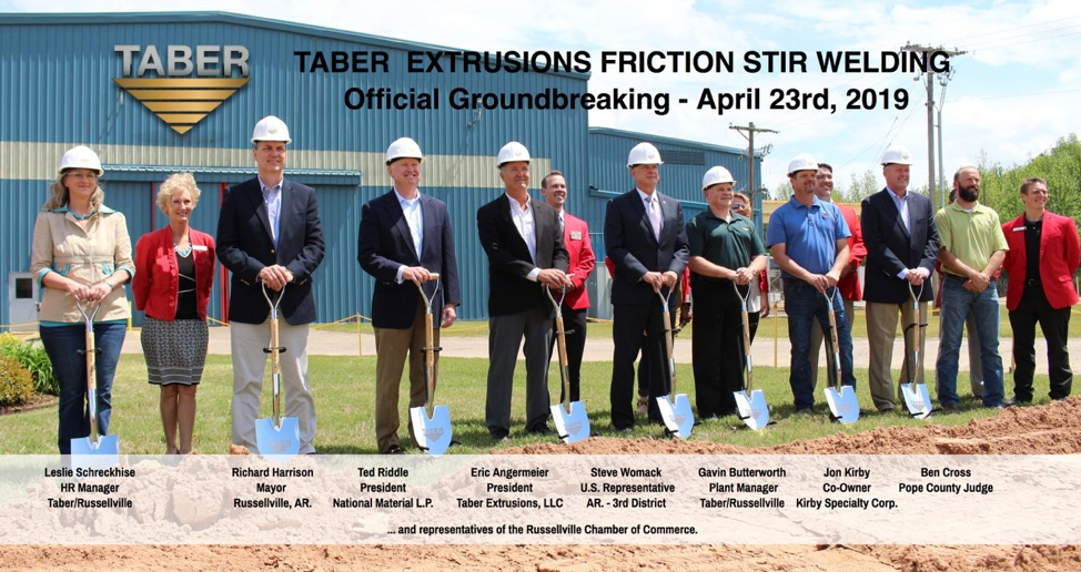 Individuals at Taber's groundbreaking ceremony, sporting white hardhats and posing with shovels on a sunny day at the Taber Extrusions Russellville, Arkansas facility.