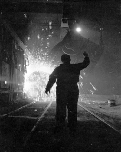 Black & white image of a silhouetted steel worker gesturing upwards as molten metal pours forth from a vat in front of him, sending glowing sparks in every direction.