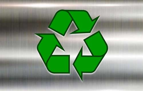 "3 green arrows pointing towards each other shaped in a triangle, commonly known as the ""recycle"" symbol, on a shiny steel background."
