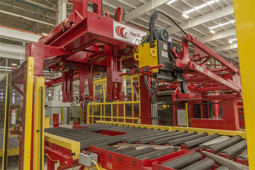 An impressive, fire-engine red piece of machinery known as a Red Bud Slitter housed in NMM's brightly lit manufacturing facility, as part of their advanced high-strength steel slitting line.