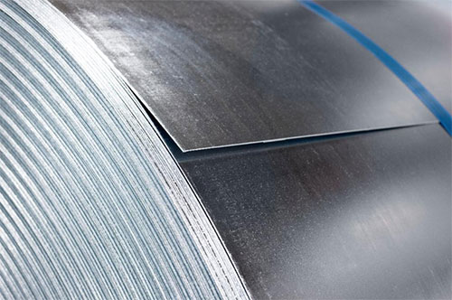 Close up shot of a shining galvanized roll of steel held tight by a blue band.