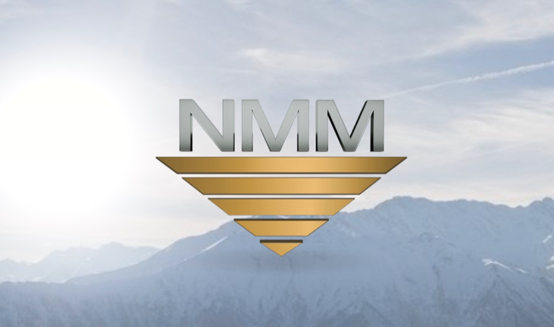 "The official National Material Mexico Logo which consists of ""NMM"" written in large, silver 3-D letters with shadow effect to create depth, and underneath a backwards pyramid made up of four upside-down, golden trapezoids that gradually reduce in length until they reach a triangle point set in the forefront of a beautiful luminous winter mountain backdrop."