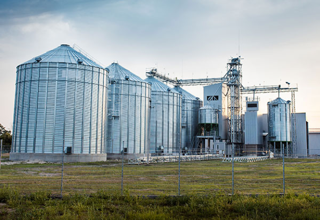 A wide angle of four large galvanized agricultural grain bins on an overcast day.