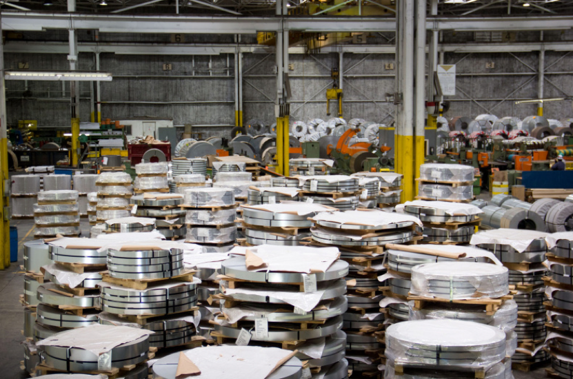 One of National Material Company's steel processing plants, with many stacks of packaged rolled steel in a factory setting.