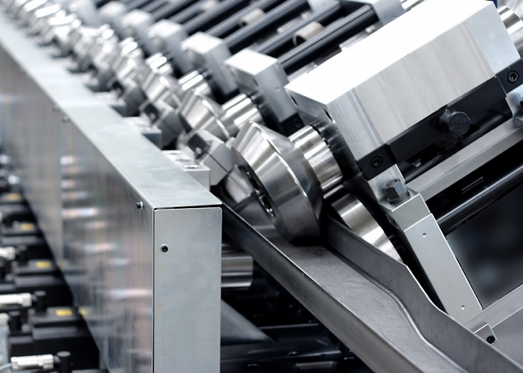 An up-close, side-angle of a clean and shiny steel roll forming machine.