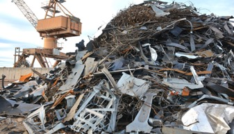 A large pile of scrap metal in a scrap metal yard, with an orange crane in the background