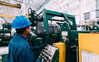 National Material Company's partner company, National Material of Mexico's brightly lit steel processing facility. A steel-processing equipment operator wearing all blue protective gear and clothing carefully monitors his machinery.